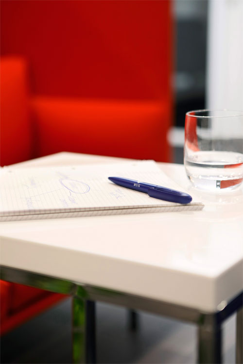 Close-up of table with notepad, pencil and glass. In the background a bright red sofa