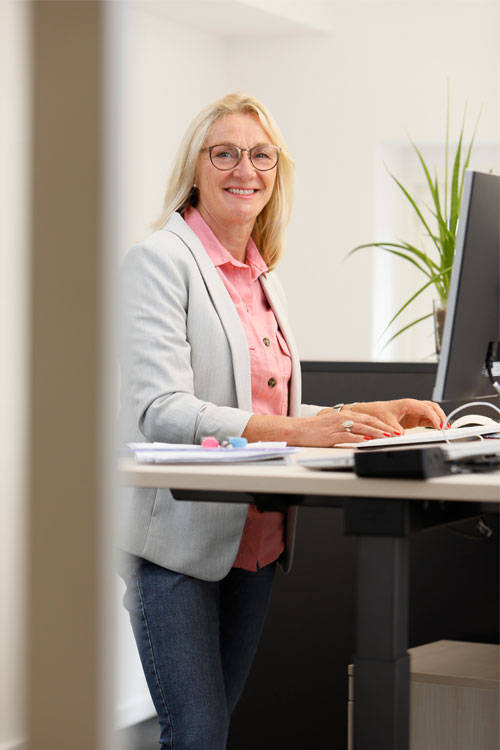 MSIGEU employee Andrea Pähler standing at an office table and smiling into the camera